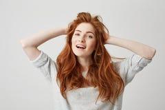 微笑愉快的年轻美丽的红头发人的女孩画象看在白色背景的照相机感人的头发 图库摄影