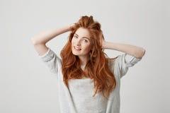 微笑愉快的年轻美丽的红头发人的女孩画象看在白色背景的照相机感人的头发 免版税库存图片