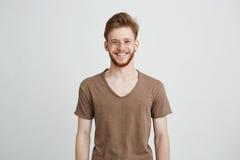 微笑愉快的快乐的年轻的人画象有胡子的看在白色背景的照相机 免版税图库摄影
