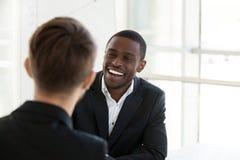 微笑愉快的黑人的工作者有与同事的谈话 免版税库存图片