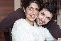 微笑愉快的年轻的夫妇拥抱和室内 免版税图库摄影