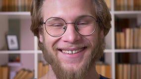 微笑成人可爱的男生特写镜头射击玻璃的快乐地看照相机在学校图书馆中 股票录像