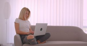 微笑成人白种人白肤金发的女性特写镜头画象使用看照相机的膝上型计算机的愉快地坐 股票视频
