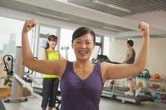 微笑成熟显示她力量的妇女在锻炼以后在健身房,武装上升和屈曲肌肉 免版税库存照片