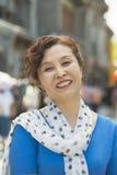 微笑成熟的妇女画象户外,北京 免版税库存照片