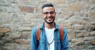 微笑户外在砖墙附近的吸引人阿拉伯人慢动作画象  股票视频