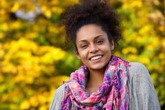 微笑户外在秋天的友好的少妇 免版税库存图片