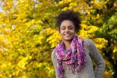 微笑户外在秋天的美丽的年轻黑人妇女 免版税库存照片