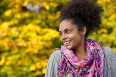 微笑户外在秋天的年轻非裔美国人的妇女 免版税库存图片