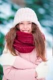 微笑户外在美好的冬天雪天的美丽的女孩画象 免版税库存图片