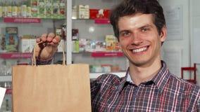 微笑拿着购物袋对药房的愉快的英俊的人 库存照片