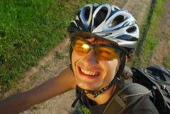 微笑接近的骑自行车者  免版税库存图片
