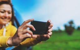 微笑旅游女孩在一自动汽车照相selfie的一个开窗口里在流动智能手机的,看在照相机小配件的人 库存图片
