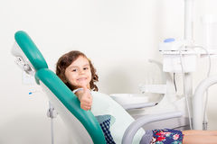 微笑显示好标志对牙齿的逗人喜爱的小女孩 免版税库存照片