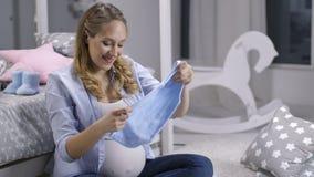 微笑期待拿着新出生的onesie的妇女 影视素材