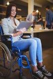 微笑残疾的女实业家,当使用数字式片剂时 免版税库存图片
