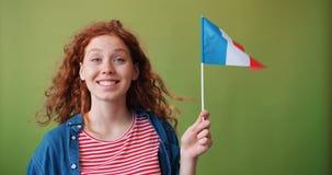 微笑法国的美丽的十几岁的女孩藏品的旗子看照相机 股票录像