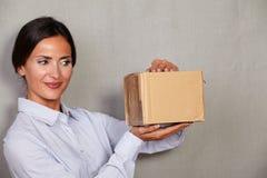 微笑深色的夫人,当打开包裹时 免版税图库摄影