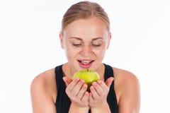 微笑用一个绿色苹果的美丽的少妇在她的手上 图库摄影