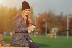微笑用咖啡的年轻时髦的妇女在公园 库存照片