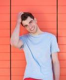 微笑用在头发的手的一个英俊的年轻人的画象 免版税库存照片