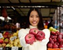 微笑用红色苹果的少妇在市场商店 免版税库存图片
