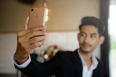 微笑由智能手机的商人selfie 免版税库存照片