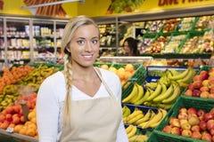 微笑由果子条板箱的确信的女推销员在超级市场 免版税库存图片