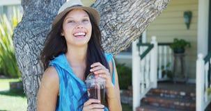 微笑由树的逗人喜爱的混合的族种妇女 免版税库存图片