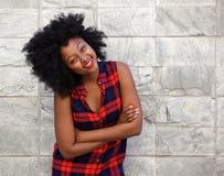 微笑由石墙的年轻非洲妇女 库存照片
