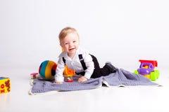 微笑男孩坐有玩具的毯子在白色背景 免版税图库摄影