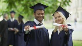 微笑男性和女性的毕业生显示文凭和,完全高等教育 股票视频