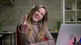 微笑白种人女性的办公室工作者特写镜头画象在膝上型计算机前面的拉扯她的胳膊和显示赞许 影视素材