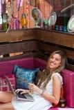 微笑白肤金发与膝上型计算机和茶杯在长沙发。 免版税图库摄影