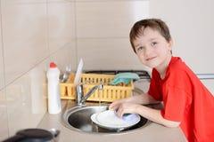 微笑的七岁的男孩洗盘子 免版税库存照片