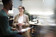 微笑的业务经理谈话与雇员 免版税库存图片