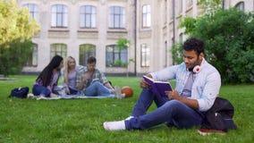 微笑的两种人种的男学生坐草和读有趣的书 库存图片