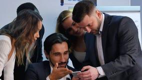 微笑的事务合作与智能手机一起使用,观看somethng有趣在办公室 免版税库存照片