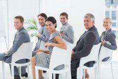 微笑的事务合作看照相机在会议期间 库存图片