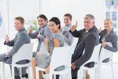 微笑的事务合作看照相机在会议期间 免版税库存图片