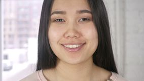 微笑的亚洲妇女面孔,看照相机的女孩在办公室 股票录像