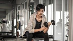 微笑的亚洲短发妇女健身哑铃举 exercis 图库摄影