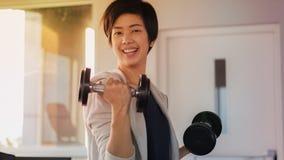 微笑的亚洲短发妇女健身哑铃举 exercis 库存照片