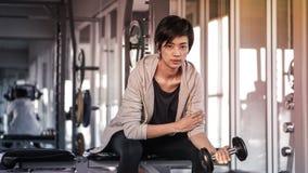 微笑的亚洲短发妇女健身哑铃举 exercis 免版税库存图片