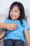 微笑的亚裔中国小女孩由有stethos的医生审查 图库摄影