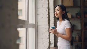 微笑的亚裔妇女喝看起来的茶站立在窗口附近和外部享受美丽的景色和休闲 影视素材