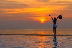 微笑的亚裔妇女愉快在放松在游泳池、在日落的旅行在海附近和海滩的大帽子 库存照片