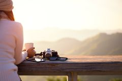 微笑的亚裔妇女饮用的咖啡和茶和在太阳坐拍照片并且放松室外在轻的阳光下享用她温暖 库存照片