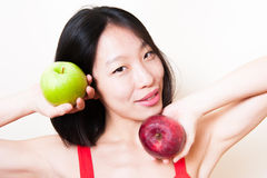 微笑的亚洲妇女关闭用在白色的绿色和红色苹果 库存图片