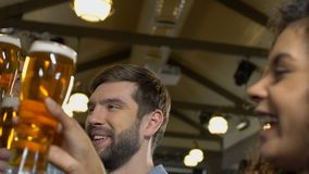 微笑的人使叮当响的啤酒杯,庆祝喜爱的队胜利的爱好者 影视素材